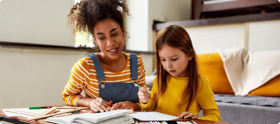 nounou qui aide aux devoirs au domicile des parents de la petite fille